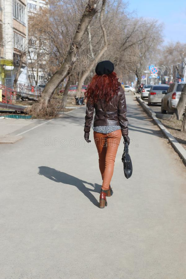 Young woman in leather jacket and beret goes down street royalty free stock photos