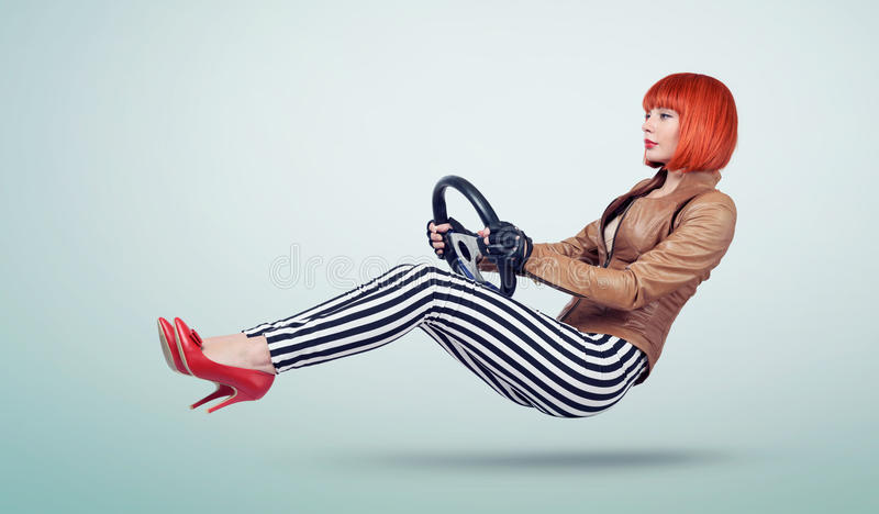 Young woman in a leather jacket and gloves driver car with a wheel, auto concept.  royalty free stock images