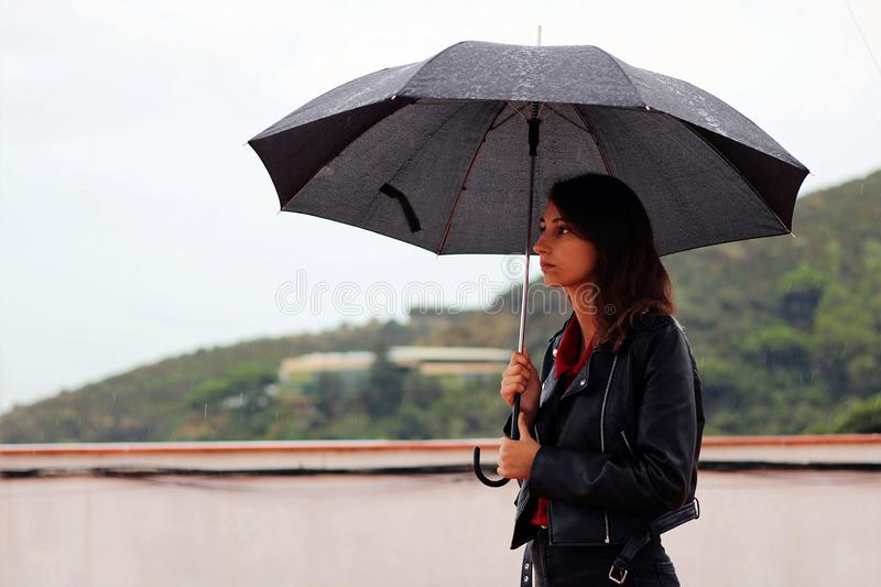 Young woman with a leather jacket holds open black umbrella in his hand under the rain stock photography
