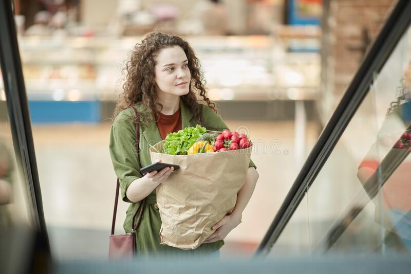 Young Woman Leaving Grocery Store royalty free stock images