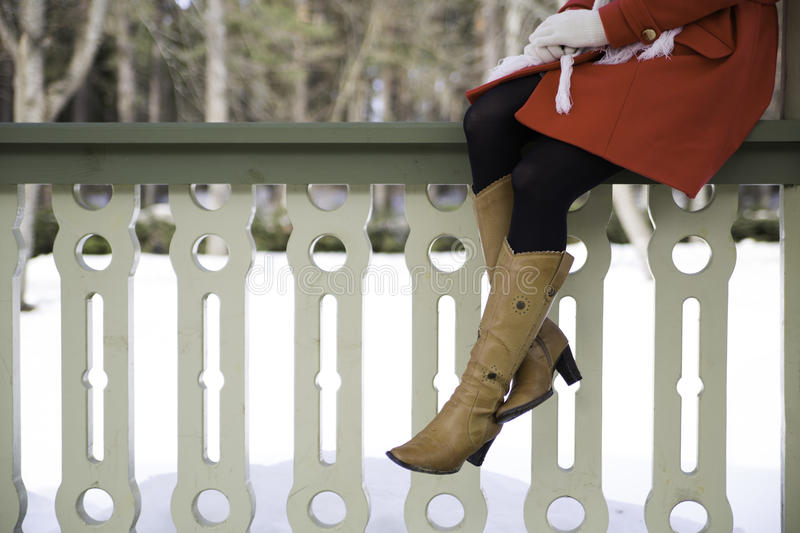Woman legs with boots at terrace boundary. Young woman legs with boots at terrace boundary royalty free stock photography