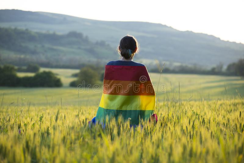 Young woman with LGBT flag. Woman holding a Gay Rainbow Flag over blue summer sky. Bisexual,gay, lesbian, transsexual symbol. Happiness, freedom and love concept royalty free stock images