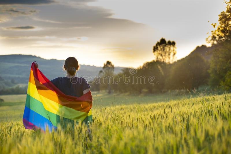 Young woman with LGBT flag. Woman holding a Gay Rainbow Flag over blue summer sky. Bisexual,gay, lesbian, transsexual symbol. Happiness, freedom and love concept royalty free stock photos