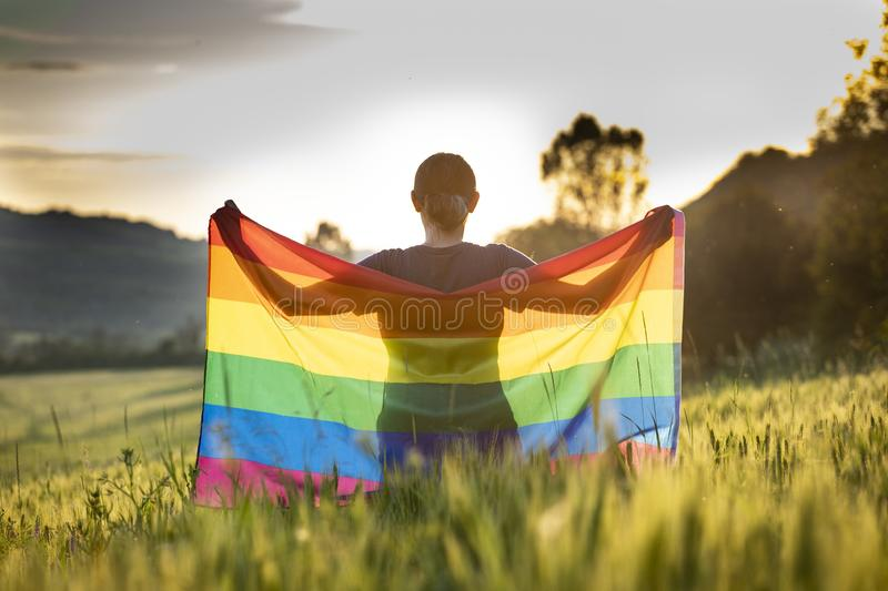 Young woman with LGBT flag. Woman holding a Gay Rainbow Flag over blue summer sky. Bisexual,gay, lesbian, transsexual symbol. Happiness, freedom and love concept royalty free stock photography