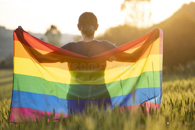 Young woman with LGBT flag. Woman holding a Gay Rainbow Flag over blue summer sky. Bisexual,gay, lesbian, transsexual symbol. Happiness, freedom and love concept royalty free stock image