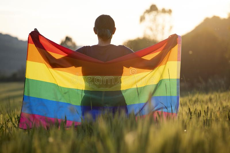 Young woman with LGBT flag. Woman holding a Gay Rainbow Flag over blue summer sky. Bisexual,gay, lesbian, transsexual symbol. Happiness, freedom and love concept stock images