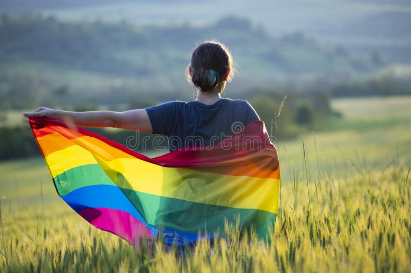 Young woman with LGBT flag. Woman holding a Gay Rainbow Flag over blue summer sky. Bisexual,gay, lesbian, transsexual symbol. Happiness, freedom and love concept stock photos