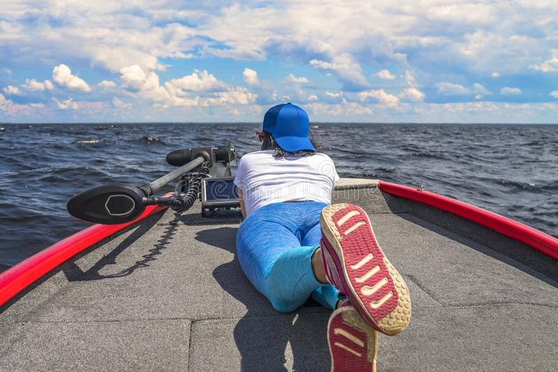 Young woman lie on fishing boat with fish finder, echolot, sonar aboard royalty free stock image