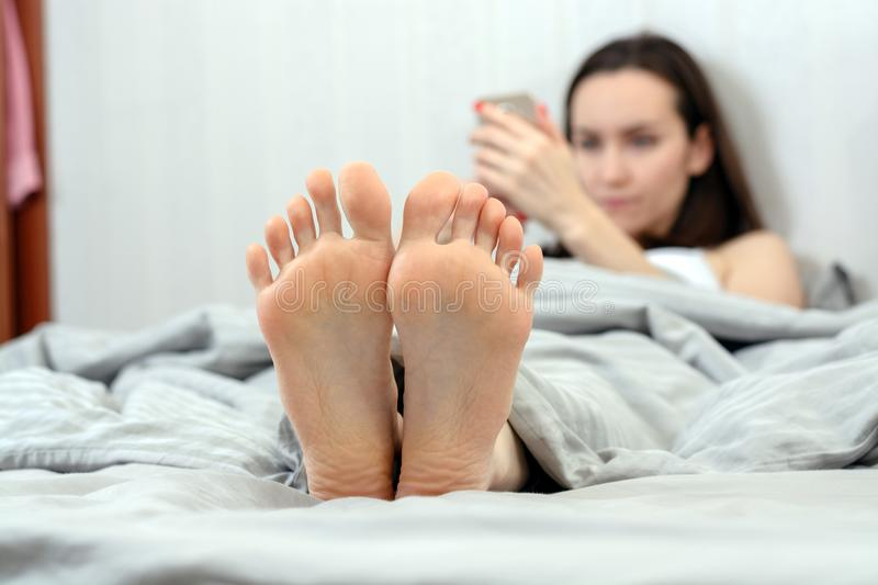 A young woman lies in bed and communicate in social networks via smartphone. focus on the feet. shallow depth of field royalty free stock photos