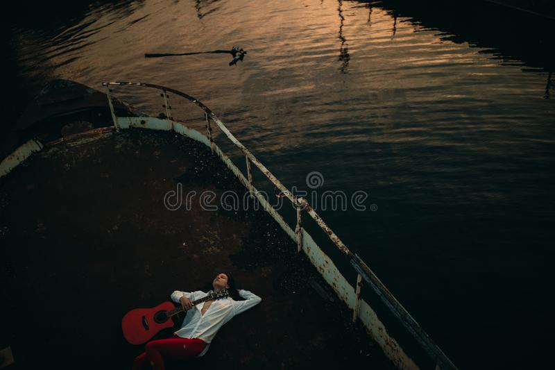 A young woman lies with guitar on an old abandoned ship against water background stock images
