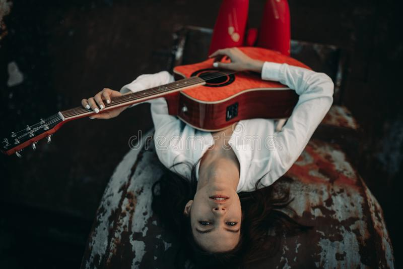 A young woman lies and plays guitar on an old abandoned ship in white shirt and red holey tights stock photos