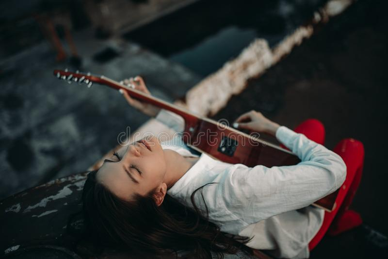 A young woman lies and plays guitar on an old abandoned ship in white shirt and red tights royalty free stock images