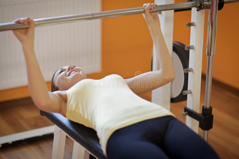 Young woman lift a barbell on a bench royalty free stock images