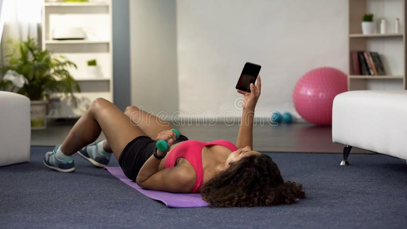 Young woman lifting dumbbell with one hand, holding phone in another, fitness royalty free stock images