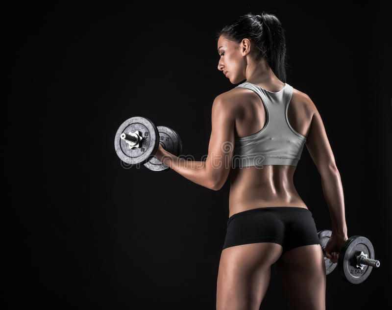 Young woman lifting the dumbbells royalty free stock photos