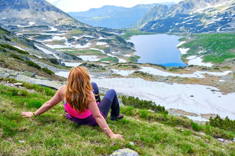 Young woman with light brown and copper strands of hair, and bright fuchsia shirt, looking towards mountain Lake Bucura, Retezat. stock images