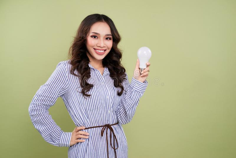 Young woman with light bulb on a green background stock images