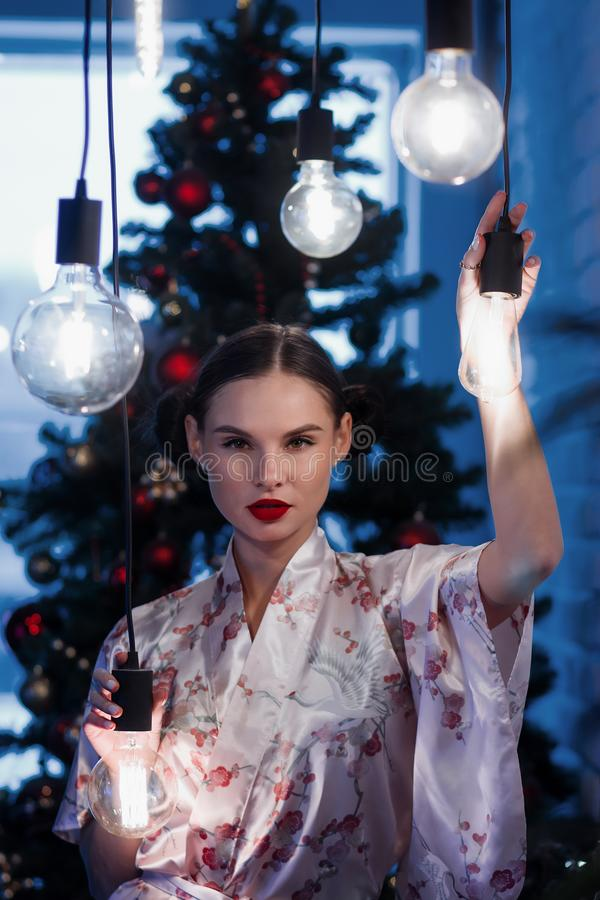 Young woman with light bulbs against Christmas tree royalty free stock image
