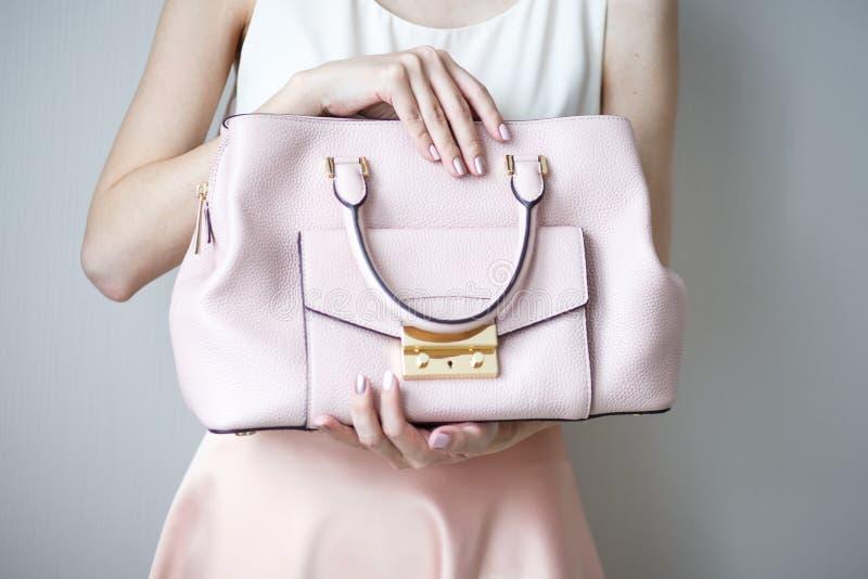 Young woman with light pink handbag, romantic casual style. Young woman with light pink trendy handbag, romantic casual look style, close-up photo royalty free stock photography