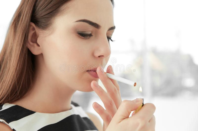 Young woman lighting cigarette. At home stock photo