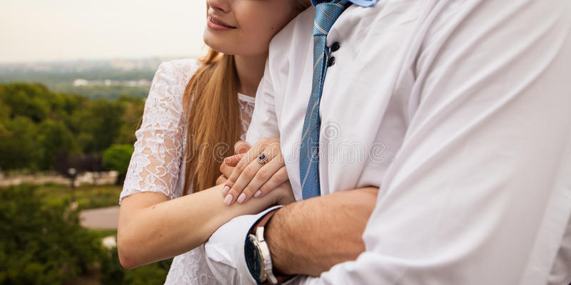 Young woman links arms with her man. Young women links arms with her man. Happy couple stands on hill with beautiful view behind stock photo