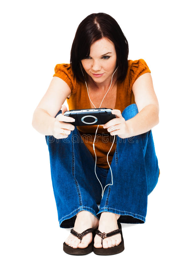 Young woman listening media player. Young woman listening to music on an media player isolated over white royalty free stock image