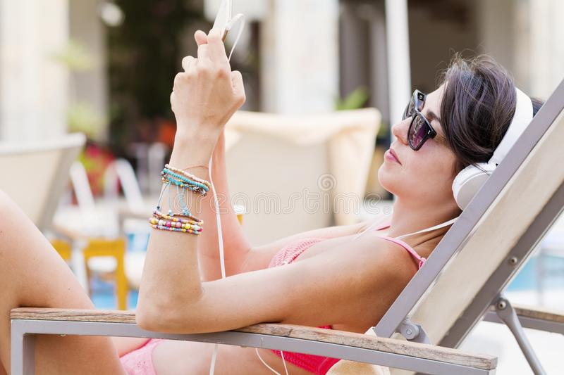 Young Woman Listening Music at the Beach. Happy young woman relaxing on the beach. Summer vacation royalty free stock images