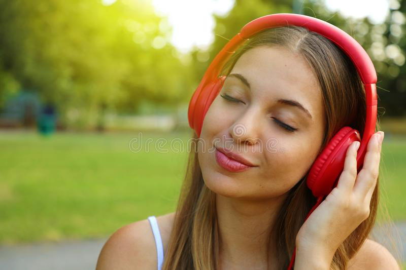 Young woman listening music in headphones in the city. Copy space stock photos