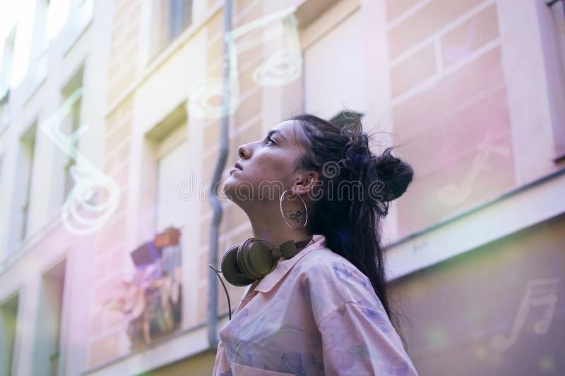Young woman listening music on the street stock image
