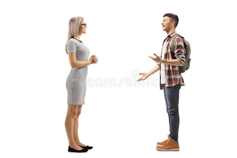 Young woman listening to a male student explaining and gesturing with hands royalty free stock image