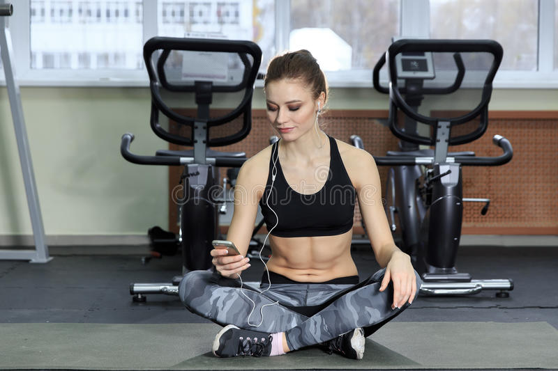 Young woman listening to music with earphones in the gym. stock image