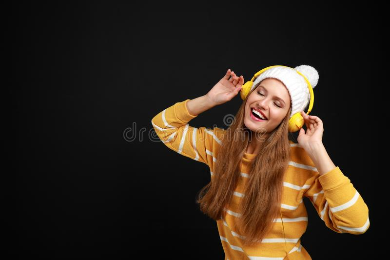 Young woman listening to music with headphones on black background royalty free stock photography