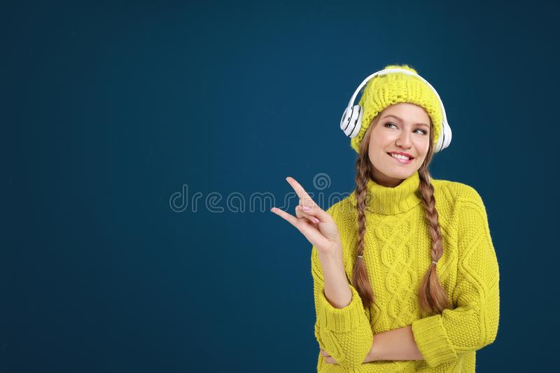 Young woman listening to music with headphones on blue background, space for text royalty free stock image