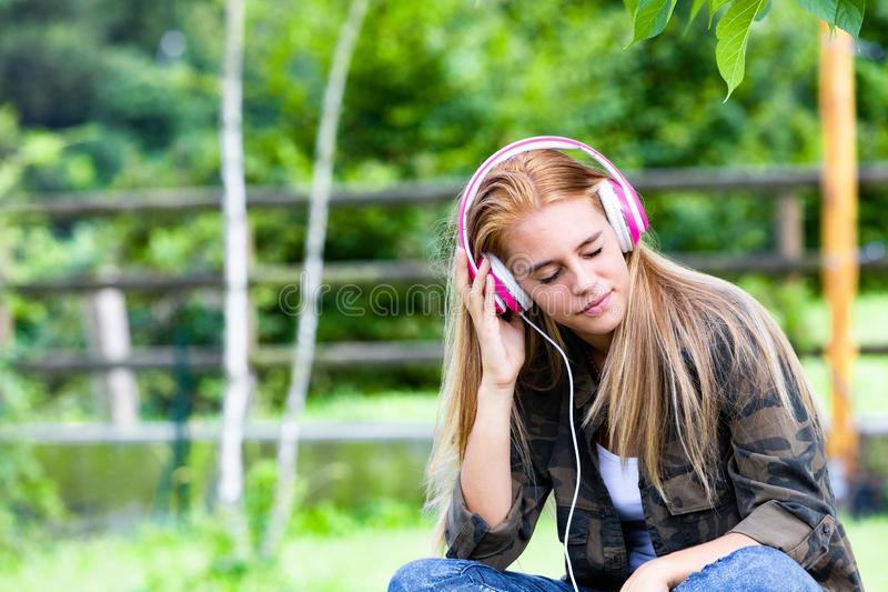 Young woman listening to music on headphones. Young woman in countryside sat listening to music on headphones royalty free stock images