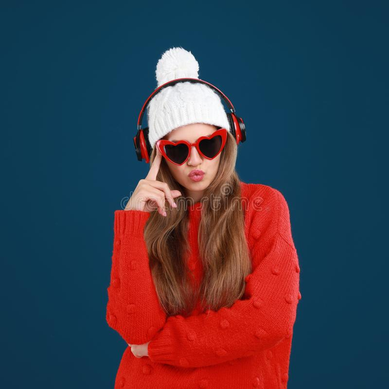 Young woman listening to music with headphones on blue background royalty free stock images