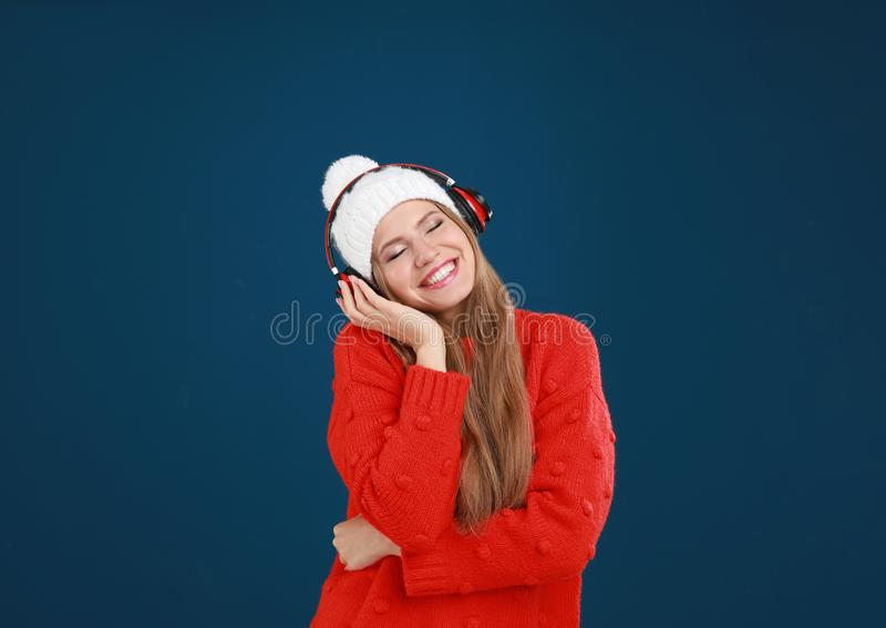 Young woman listening to music with headphones on blue background stock photography