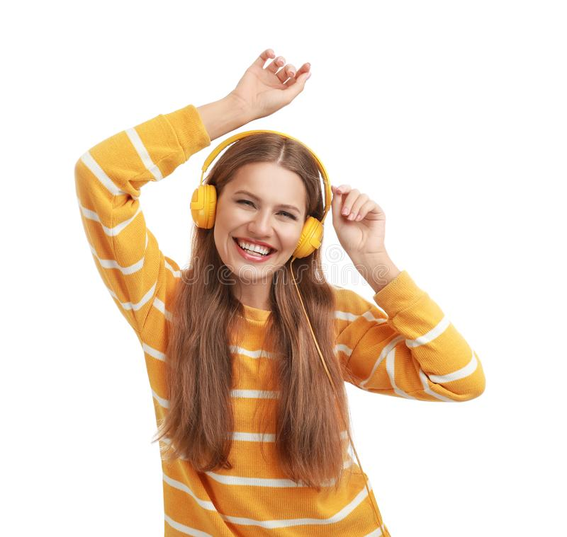 Young woman listening to music with headphones on background stock images