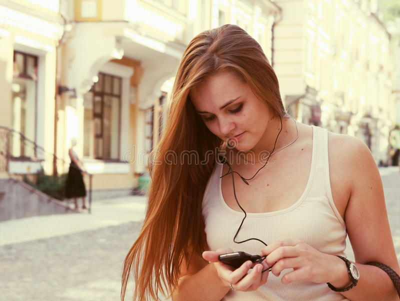 Download Young Woman Listening To Music Outdoors Stock Photo - Image of person, toned: 26477186