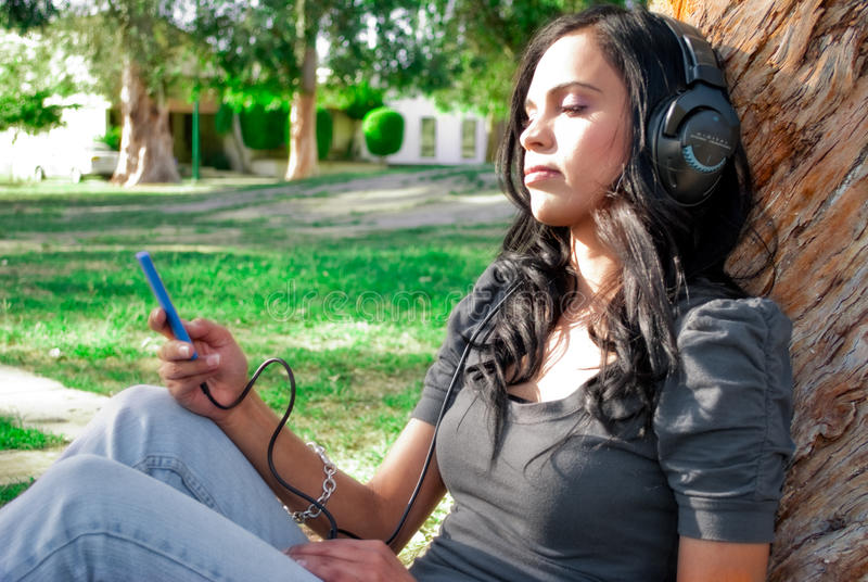 Young woman listening to music at a park. Young woman listening to music with headphones at a park, next to a tree royalty free stock photos