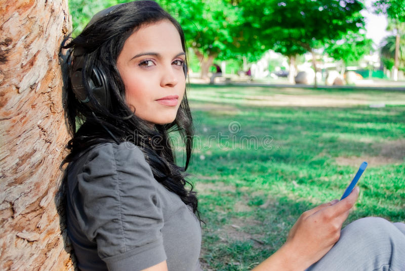 Young woman listening to music at a park. Young woman listening to music with headphones at a park, next to a tree stock photo
