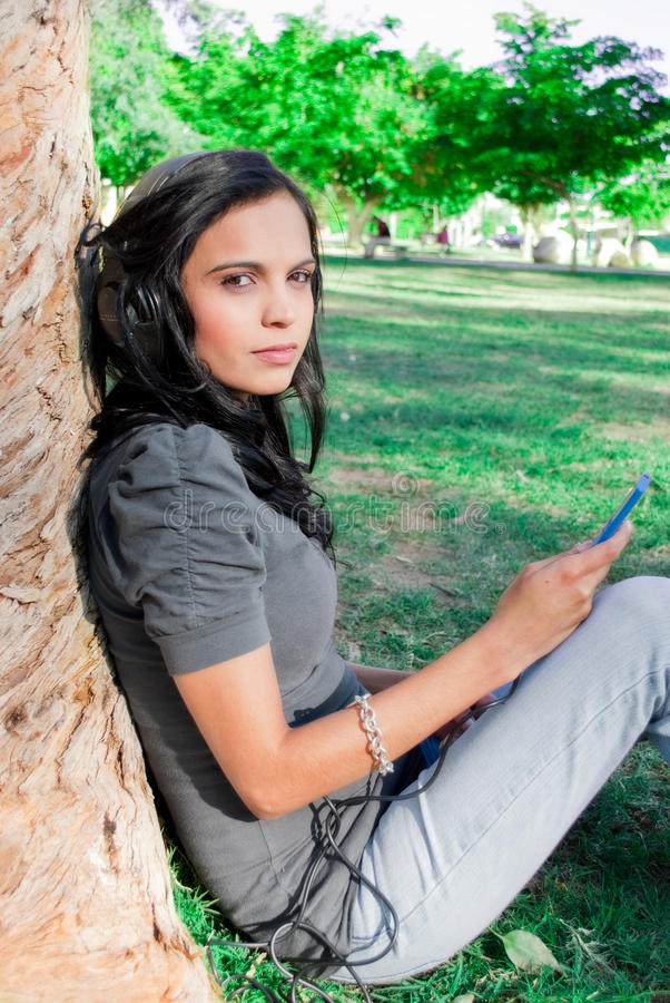 Young woman listening to music at a park. Young woman listening to music with headphones at a park, next to a tree royalty free stock photo