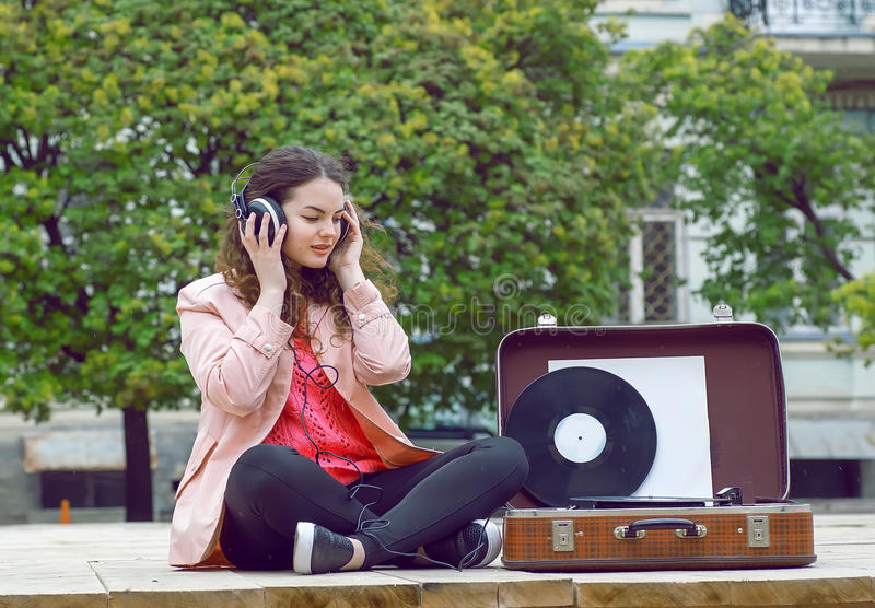 Young woman listening to music in a park. Portrait of girl feeling good with songs on old stereo vinyl system stock photo