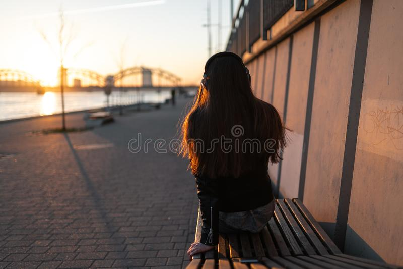 Young woman listens to music in closed headphones through her phone wearing a leather jacket and jeans at a sunset near stock photo