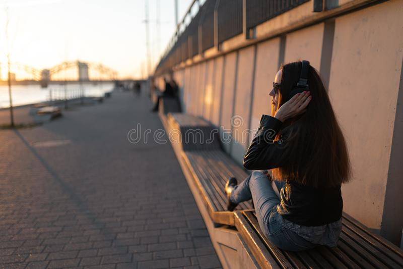 Young woman listens to music in closed headphones through her phone wearing a leather jacket and jeans at a sunset near stock image
