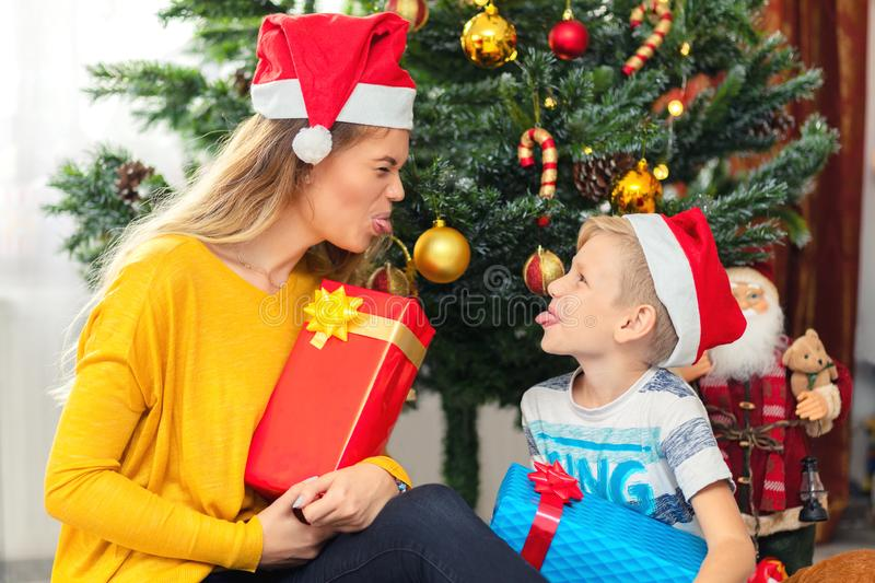 Happy mom and son wearing santa hat sharing presents under tree stock image