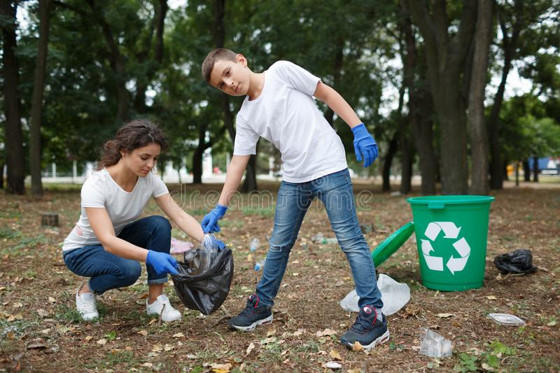 A young woman and a little boy picking up the trash and putting it in a black garbage bag on a blurred park background. stock photography