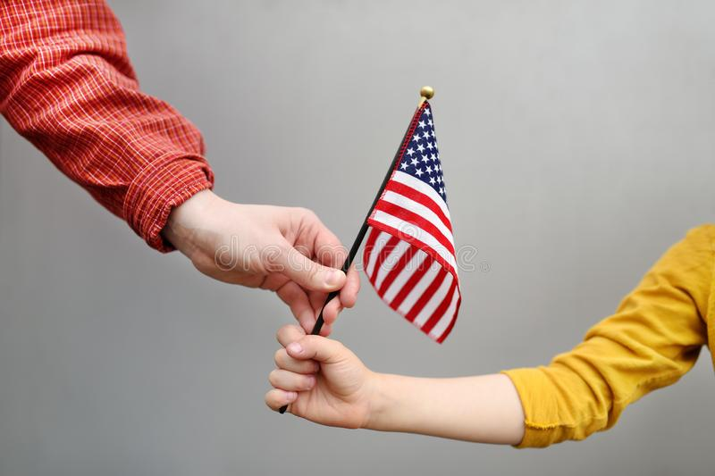 Young woman and little child holding american flag. Independence Day concept stock photos