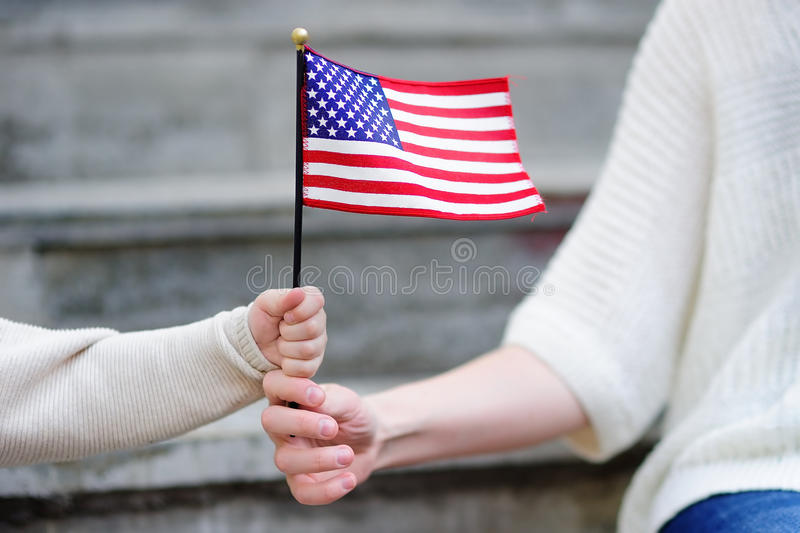 Young woman and little child holding american flag stock image