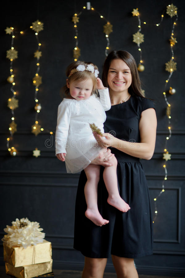 Young woman with the little daughter on hands. Young women with the little daughter on hands. Ruddy baby is dressed in a white dress, on the head of her a royalty free stock photos