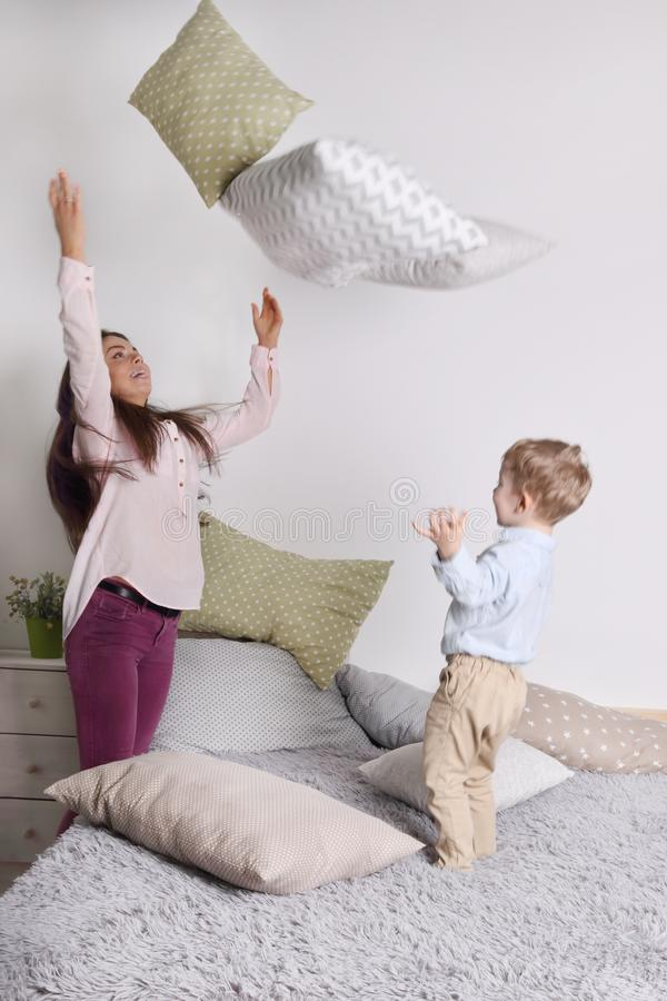 Young woman, little son throw pillows on grey bed stock images